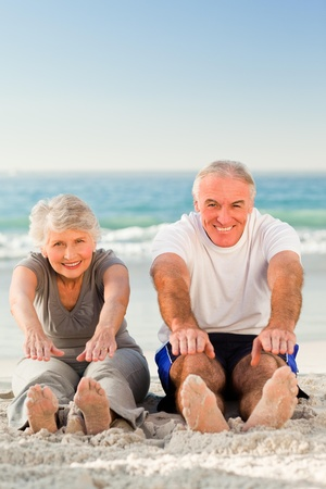 one senior: Couple doing their streches at the beach