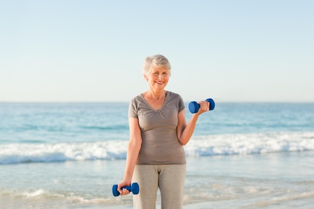Woman doing her exercises at the beach photo