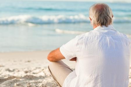 El hombre sentado en la playa Foto de archivo