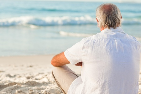 Man sitting on the beach Stock Photo