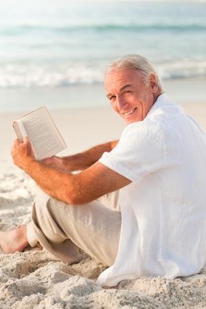Man reading a book on the beach photo