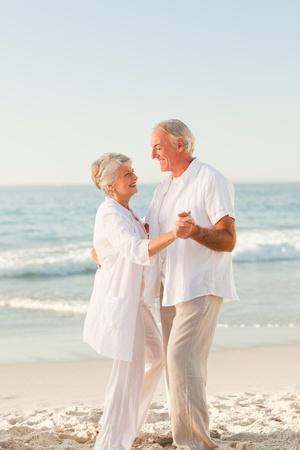 senioren wandelen: Ouderen paar dansen op het strand