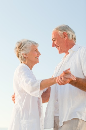 aging: Senior couple dancing on the beach