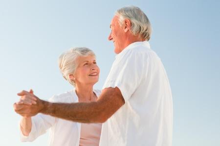 Senior couple dancing on the beach photo