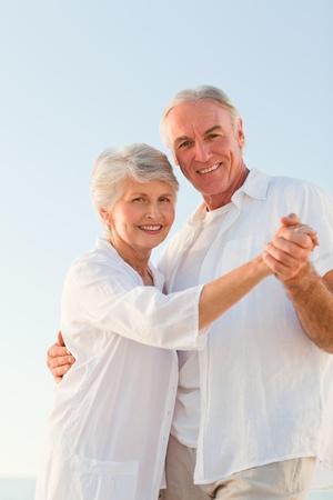 Senior paar dansen op het strand Stockfoto