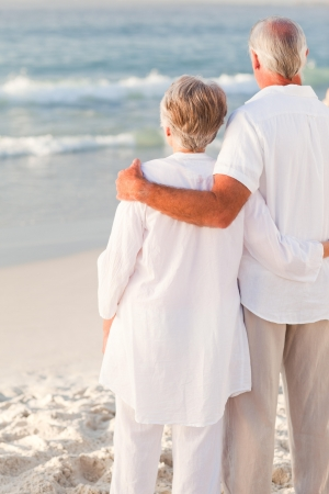 Man hugging his wife on the beach photo