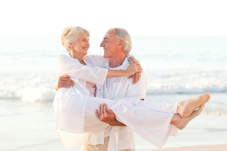 man carrying woman: Man carrying his wife on the beach