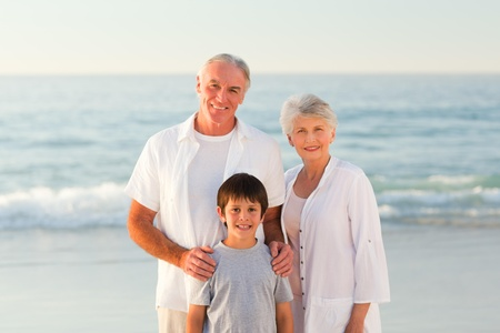 Grandparents with his grandson at the beach photo