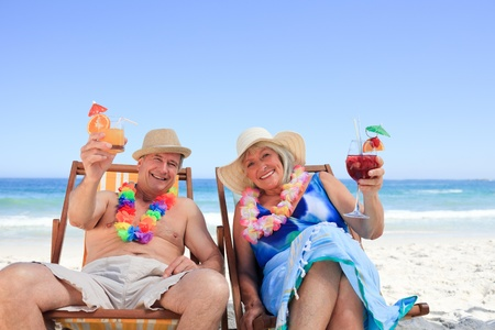 Mature couple sitting on deck chairs photo