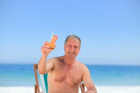 Senior man drinking a cocktail on the beach Stock Photo - 10207537
