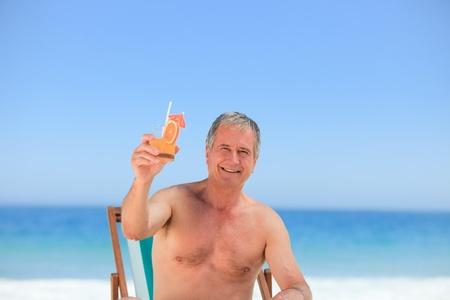 Senior man drinking a cocktail on the beach Stock Photo - 10207537