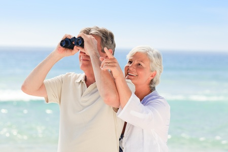 Senior couple bird watching at the beach photo