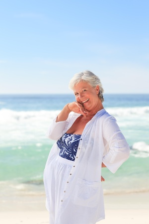 Happy retired woman on the beach photo