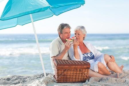 ancianos caminando: Pareja de ancianos picniking en la playa