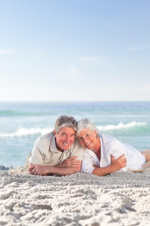 Mature couple lying down on the beach Stock Photo