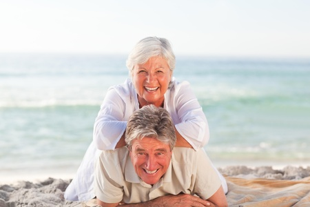 Senior couple lying down on the beach photo