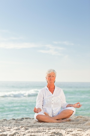 Mature woman practicing yoga on the beach photo