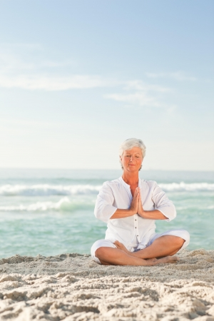 Mature woman practicing yoga on the beach Stock Photo - 10213223