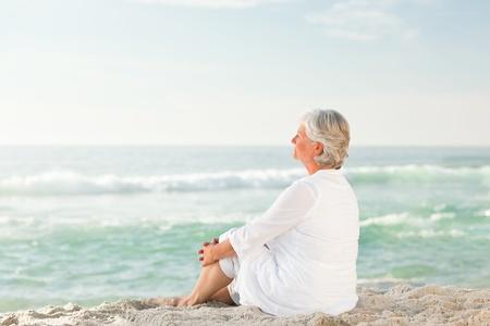 senioren wandelen: Vrouw, die zit op het strand Stockfoto