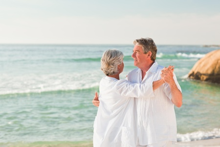 Elderly couple dancing on the beach photo