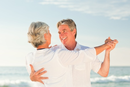 old couple walking: Mature couple dancing on the beach