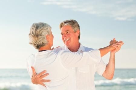 ancianos caminando: Pareja madura bailando en la playa