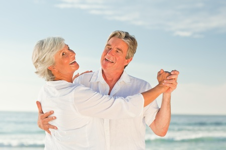 Mature couple dancing on the beach photo