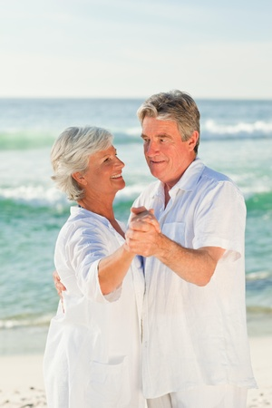 aging: Mature couple dancing on the beach