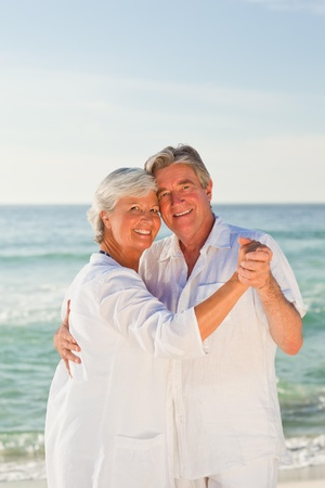 retired couple: Retired couple dancing on the beach Stock Photo