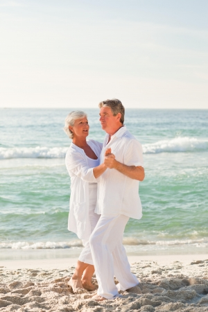 elderly couples: Retired couple dancing on the beach Stock Photo