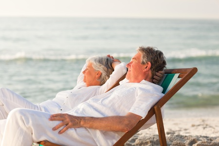 Elderly couple relaxing in their deck chairs photo