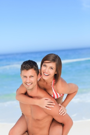 Handsome man having wife a piggyback on the beach photo