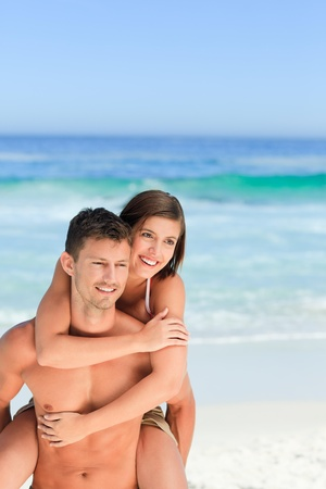Man having wife a piggyback on the beach photo