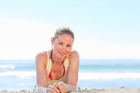 A woman sunbathing at the beach photo
