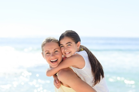 smiling sun: Mother having daughter a piggyback at the beach