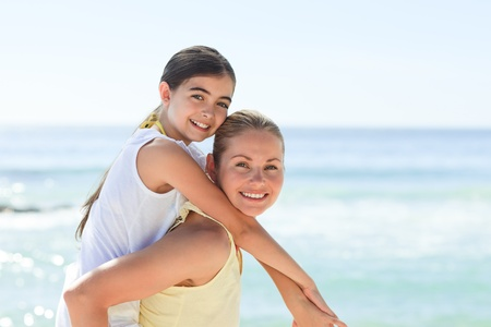 Mother having daughter a piggyback at the beach photo