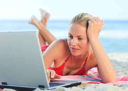 Lovely woman working on her laptop at the beach photo
