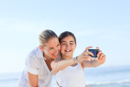compact: Little girl taking a photo of herself and her mother Stock Photo