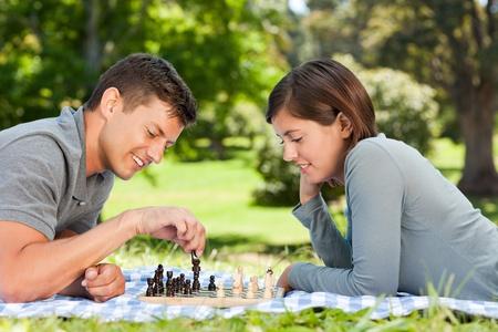 jugando ajedrez: Pareja jugando al ajedrez en el parque