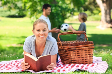 Father and son playing football while the mother is reading Stock Photo - 10218409