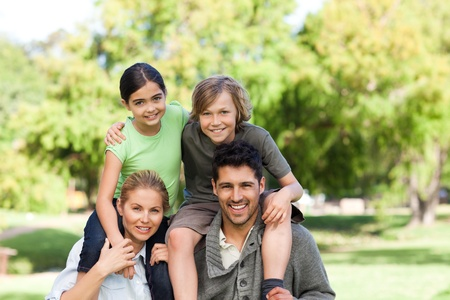 Parents giving children a piggyback Stock Photo - 10217917
