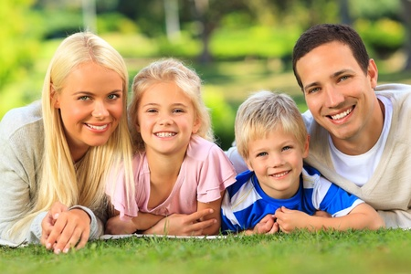 Family lying down in the park photo