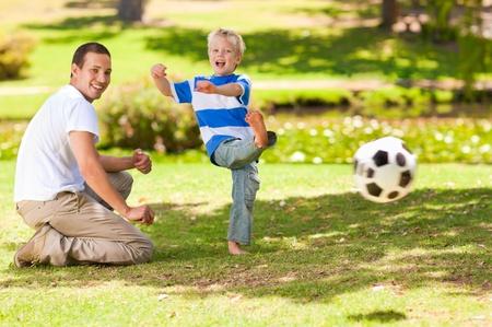 padre e hijo: Padre jugando al fútbol con su hijo
