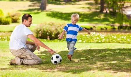 jugando futbol: Padre jugando al f�tbol con su hijo