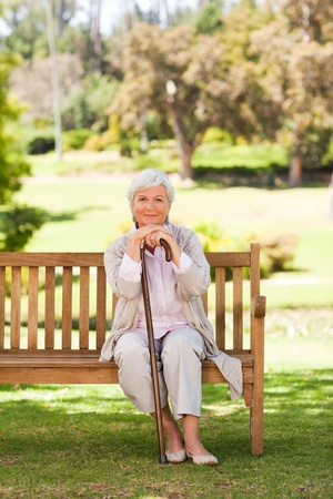 sitting on bench: Woman with her walking stick in the park