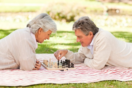 play the old park: Elderly couple playing chess
