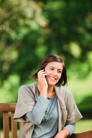 Beautiful woman phoning on the bench photo