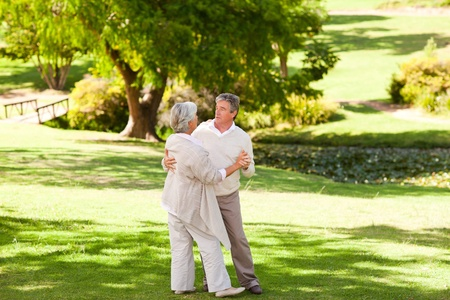 Senior couple dancing in the park photo