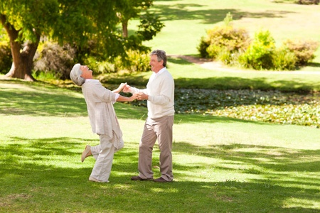 Mature couple dancing in the park photo