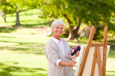 Senior woman painting in the park photo